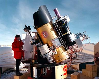 Man standing next to a large telescope in Antarctica