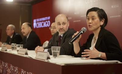 Women spekaing to a microphone with men sitting beside her at a table