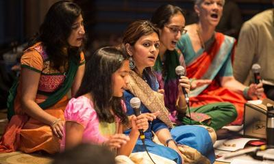 Girl speaking on microphone is surrounded by women wearing traditional clothing