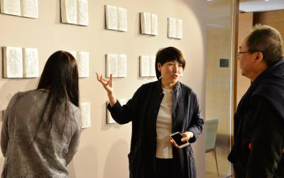 Artist Wen Fang speaks to visitors at the opening of her exhibition in the Steve Sun Gallery at the Center in Beijing