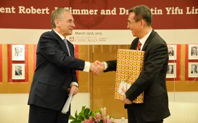 President Zimmer (left) shakes hands with Justin Yifu Lin, PhD'86 (right)
